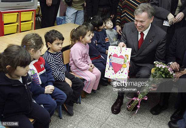 German President Horst Koehler receives a card and flowers in welcome from the children at Lilach kindergarten on February 2 2005 in Sderot Israel...