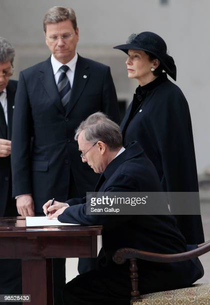 German President Horst Koehler signs a book of condolences as his wife Eva Luise Koehler and German Foreign Minister Guido Westerwelle look on at the...