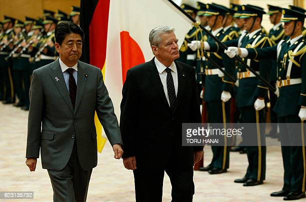 German President Joachim Gauck and Japan's Prime Minister Shinzo Abe review an honour guard before their meeting at Abe's official residence in Tokyo...
