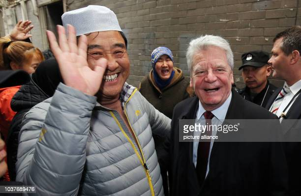 German President Joachim Gauck being greeted by a man in the muslim quater of Xi`An China 24 March 2016 The German President is on a fiveday state...