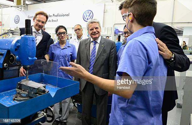 German President Joachim Gauck chats with local workers as plant manager Michael Macht looks on while touring the Volkwagen Anchieta car plant on May...