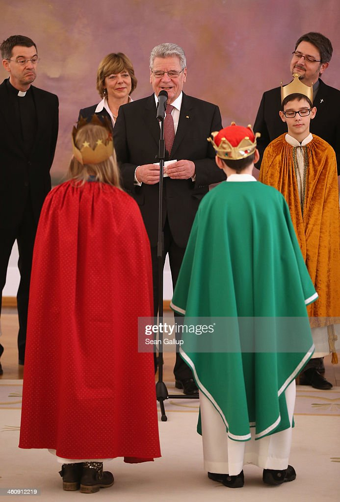 German President Joachim Gauck, flanked by his partner Daniela Schadt, welcomes children Epiphany carolers dressed as the Three Kings at Schloss Bellevue palace on January 6, 2014 in Berlin, Germany. Children across Germany dressed as the Three Kings traditionally go from house to house between the end of December and Epiphany to sing and collect donations for cahritable causes.