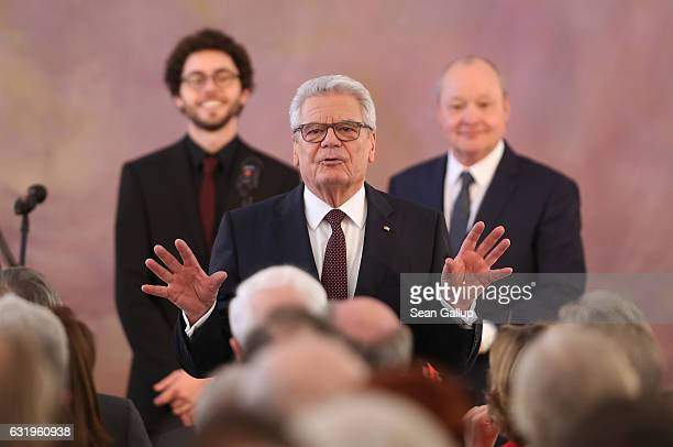 German President Joachim Gauck gestures to the audience as he stands in front of musicians after he gave a speech to mark the end of his term as...