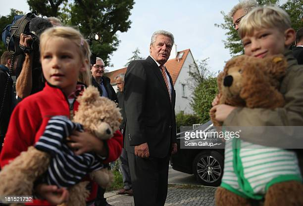 German President Joachim Gauck greets children Sophia and Erik after casting his ballot in German federal elections on September 22, 2013 in Berlin,...