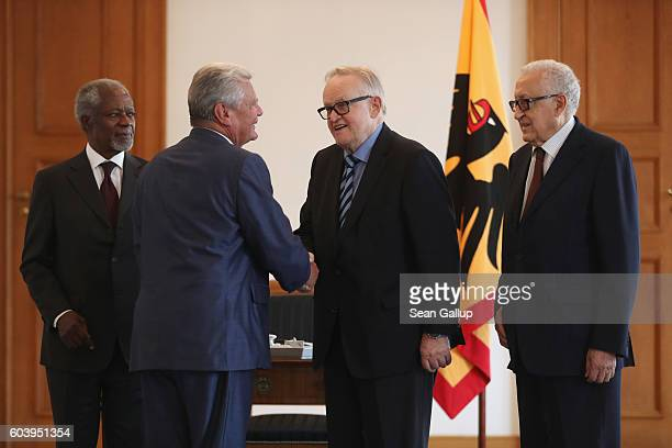 German President Joachim Gauck greets former UN General Secretary Kofi Annan former Finnish President Martti Ahtisaari and former Algerian UN...