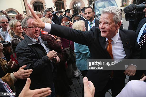 German President Joachim Gauck greets onlookers as he arrives at the Nikolaikirche church to attend a mass as part of commemorations marking the 25th...