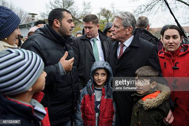 German President Joachim Gauck greets Syrian refugees at a refugee center on November 21 2013 in Friedland Germany Germany is accepting up to 5000...