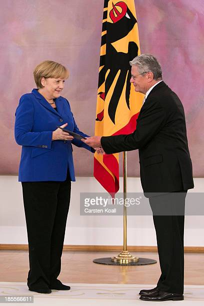 German President Joachim Gauck hands German Chancellor Angela Merkel her dismissal certificate at a ceremony for the outgoing German government at...