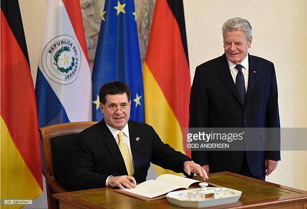 German President Joachim Gauck looks on as his Paraguayan counterpart Horacio Cartes signs his guest book at the presidential Bellevue Palace on...