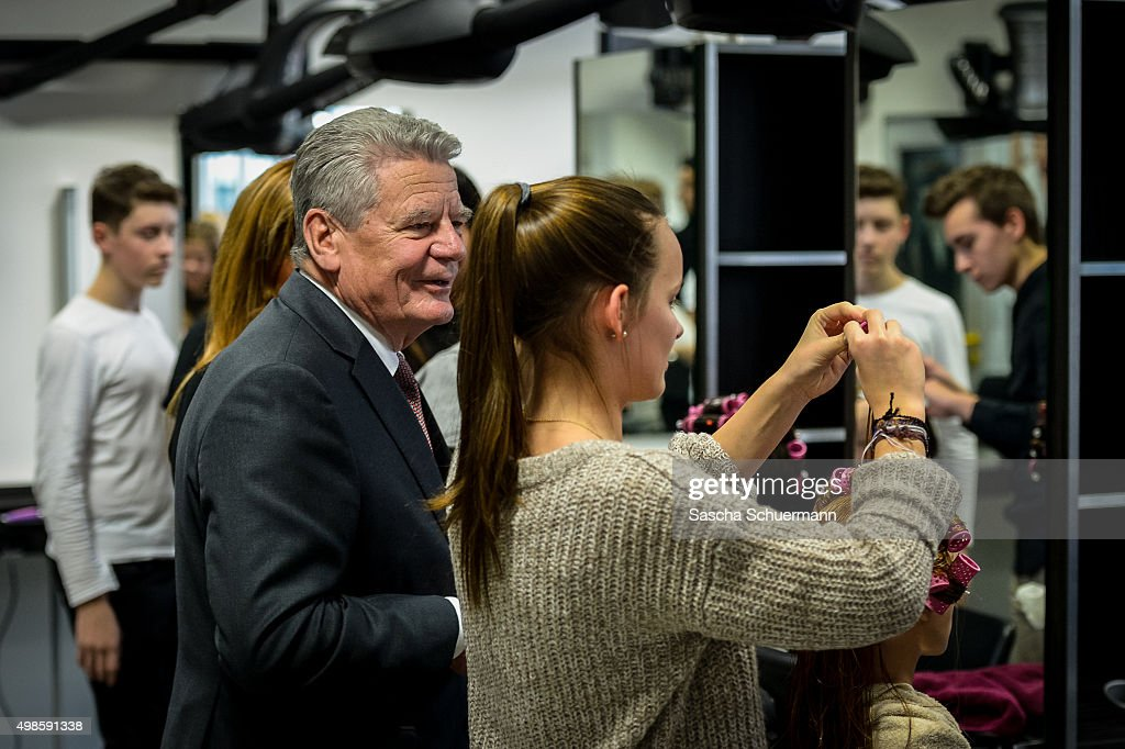 German President Joachim Gauck meets trainees working as a hairdresser with a dummy at the Vocational training center of the Chamber of Crafts (Bildungszentrum Butzweilerhof der Handwerkskammer) on November 24, 2015 in Cologne, Germany. German industry has complained in recent years of being unable to fill tens of thousands of trainee positions and some see the influx of nearly a million migrants this year as a possible opportunity to narrow the gap.