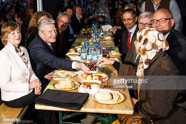 German President Joachim Gauck offers the wife of Imam figs as he and Daniela Schadt participate in the iftar meal with Muslims observing Ramadan on...