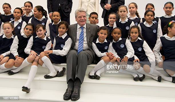 """German President Joachim Gauck poses with the children's choir group """"Coral da Gente"""", who come from a Sao Paolo slum, while touring the Volkwagen..."""