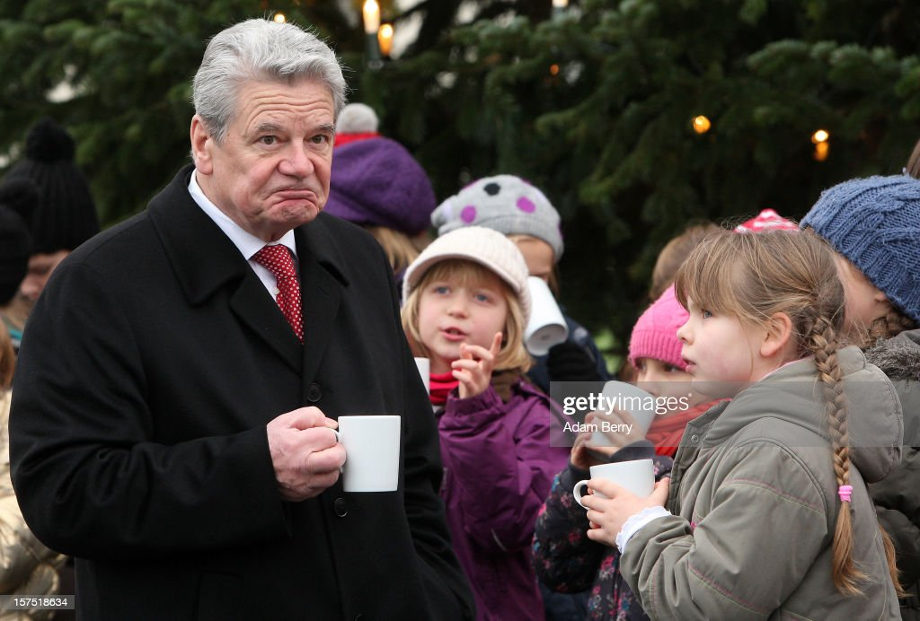 German President Joachim Gauck speaks with a child from the Carl von Ossietzky school while drinking mulled punch during the illumination ceremony for the Christmas tree at Bellevue Presidential Palace on December 4, 2012 in Berlin, Germany. The 12-meter (40-foot) tall Colorado blue spruce (Picea pungens) was planted in 1994 and is being supplied to the president for the second time by Werderaner Tannenhof Christmas tree farm in the town of Werder, just outside of the German capital.