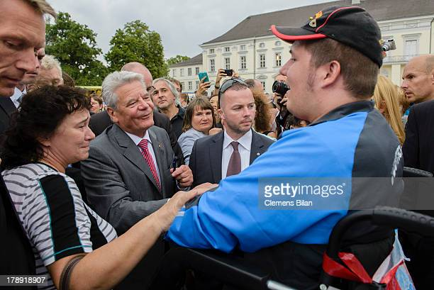 German President Joachim Gauck talks to a visitor in a wheelchair during the annual Citizens' Fest at Bellevue Palace on August 31, 2013 in Berlin,...