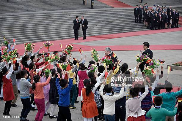 German President Joachim Gauck thanks welcoming kids while Chinese President Xi Jinping watches at the Great Hall of the People on March 21, 2016 in...