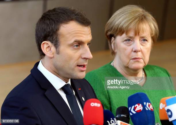 German Prime Minister Angela Merkel and French President Emmanuel Macron answer the questions of press members as they arrive to attend the EU...