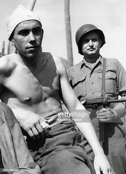 German prisoner captured without having the time to dress and wearing a handkerchief on his head in the custody of a US soldier on April 15 1945 in...