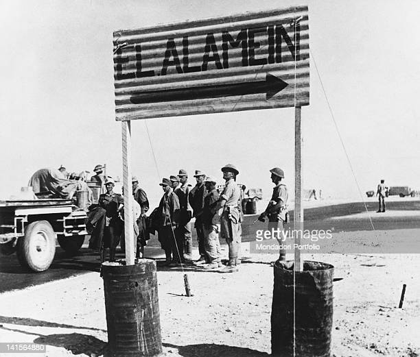 German prisoners of the Afrika Korps stopping next to a roadsign that shows the way to El Alamein after the Battle of El Alamein Egypt October 1942