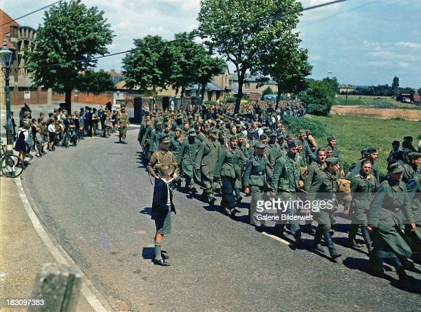 German prisoners of war are marched into the town of Gosport Hampshire guarded by British soldiers June 1944 The prisoners arrived on HM Landing Ship...