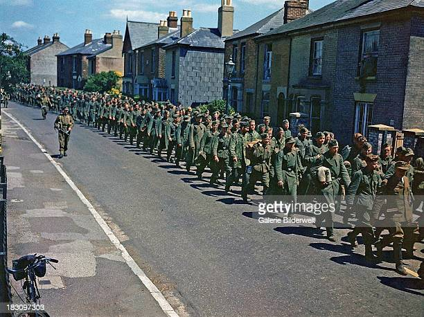 German prisoners of war are marched through the town of Gosport Hampshire guarded by British soldiers June 1944 The prisoners arrived on HM Landing...