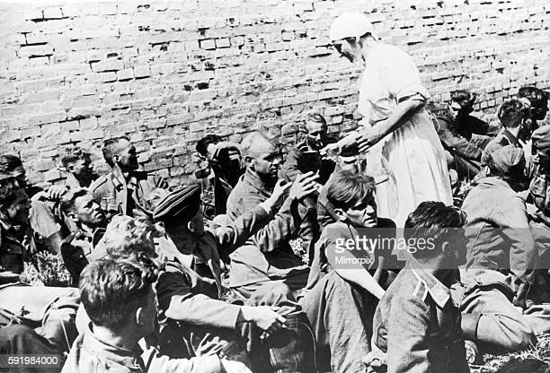 German prisoners of war captured by Russian forces in recent fighting in the Soviet Union during the Second World War are given water by a Russian...