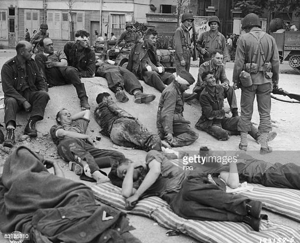 German prisoners of war, many of them captured snipers, under US Army guard at a holding point at Troyes, France, 26th August 1944.