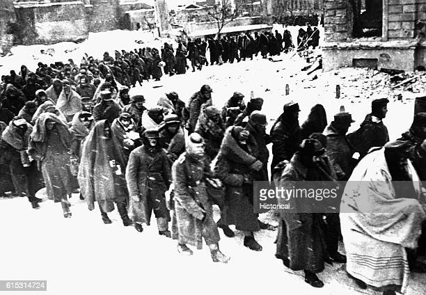 German prisoners wrapped in coats blankets or anything they could find to protect against the bitter winter weather are marched through the snowy...