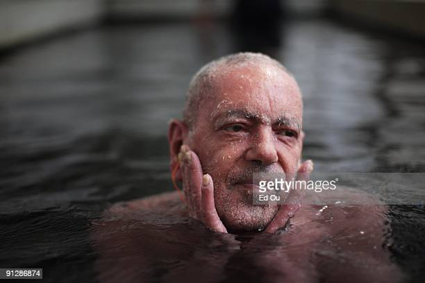 German psoriasis patient Aslan Gungor peels skin off his face while bathing in a mineralrich spring full of 'doctor fish' on September 14 2009 in...