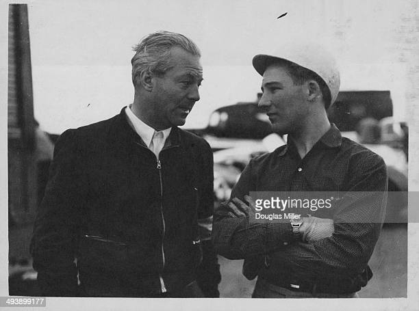 German race car driver Toni Ulmen, talking to British driver Stirling Moss, during an International Trophy practice session at Silverstone Circuit,...