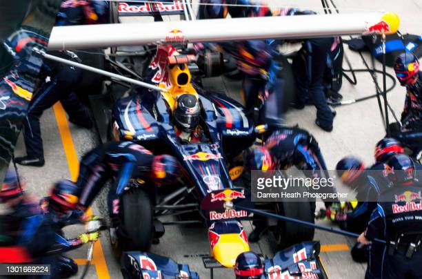 German Red Bull Racing Formula One driver Sebastian Vettel driving his Red Bull RB6 racing car during a pit stop for new tyres performed by Red Bull...