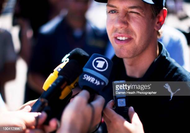 German Red Bull Racing Formula One driver Sebastian Vettel in the Formula One paddock being interviewed by journalists and television crews using...