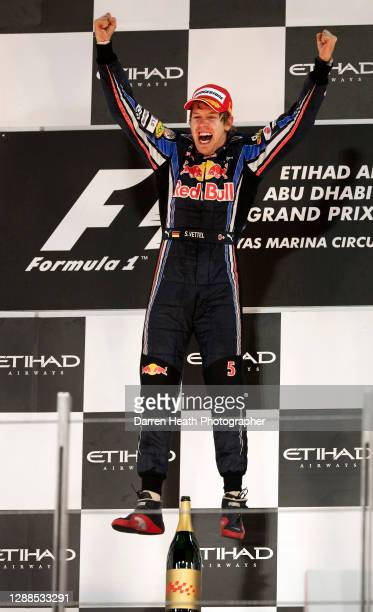 German Red Bull Racing Formula One driver Sebastian Vettel jumps for joy on the winners podium in celebration of winning both the race and securing...