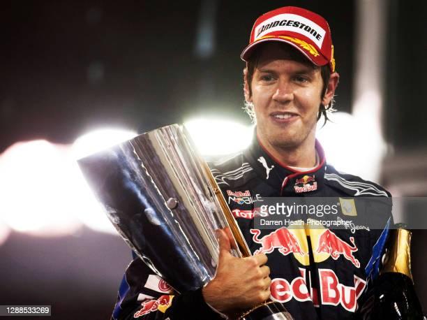 German Red Bull Racing Formula One driver Sebastian Vettel on the winners podium holding the winners trophy in celebration of winning both the race...