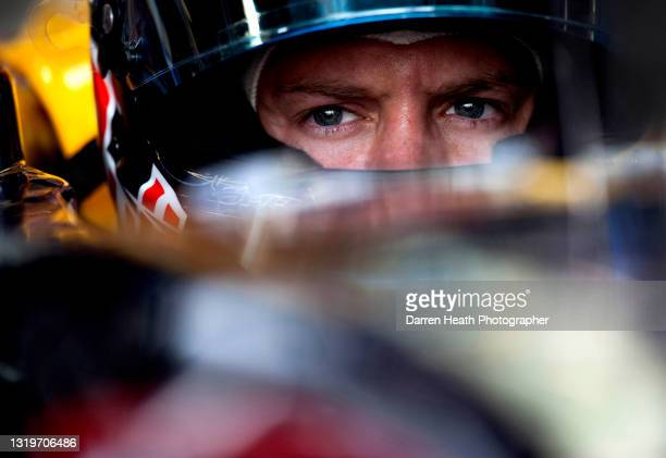 German Red Bull Racing Formula One driver Sebastian Vettel sitting in his RB7 racing car in the team's pit garage during practice for the 2011...
