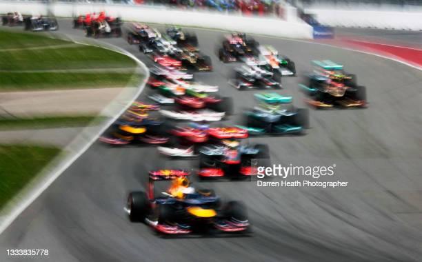 German Red Bull Racing Formula One team racing driver Sebastian Vettel driving his RB8 racing car ahead of British McLaren driver Lewis Hamilton in...