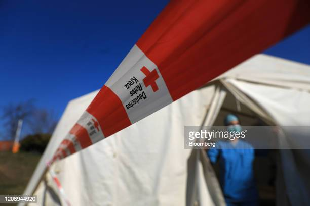 A German Red Cross cordon stands outside a testing tent set up outside the coronavirus outpatient clinic at the Paracelsus Clinic in Zwickau Germany...