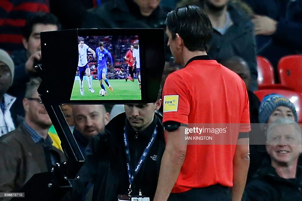 German referee Deniz Aytekin studies the VAR (Video Assistant Referee) screen to see if Italy deserve a penalty during the International friendly football match between England and Italy at Wembley stadium in London on March 27, 2018. / AFP PHOTO / Ian KINGTON