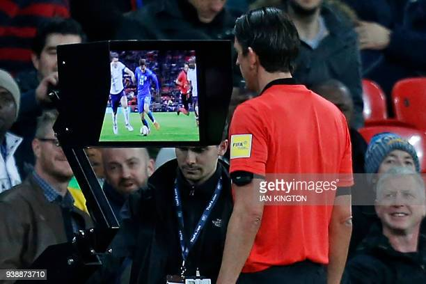German referee Deniz Aytekin studies the VAR screen to see if Italy deserve a penalty during the International friendly football match between...