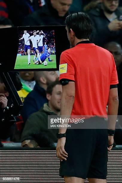 German referee Deniz Aytekin studies the VAR screen to see if Italy deserve a penalty during the International friendly football match between...