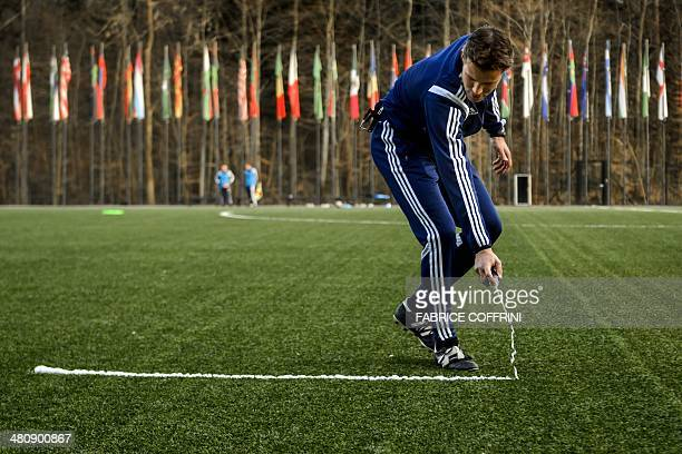 German referee Felix Brych tries the vanishing spray to mark out the distance for a defensive wall from a free-kick during a seminar for 2014 FIFA...