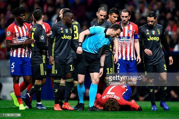 German referee Felix Zwayer checks on Atletico Madrid's French forward Antoine Griezmann as he lies on the ground during the UEFA Champions League...