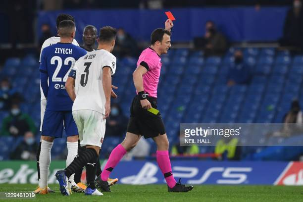 German referee Felix Zwayer holds up the red card to send off Rennes' Brazilian defender Dalbert Henrique Chagas Estevao after a second yellow card...