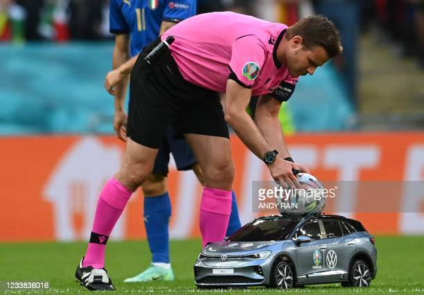 German referee Feliz Brych receives the match ball during the UEFA EURO 2020 semi-final football match between Italy and Spain at Wembley Stadium in...