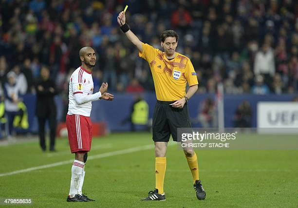 German referee Manuel Graefe shows the yellow card to Salzburg's Brazilian striker Alan during the UEFA Europa League round of 16 second leg football...