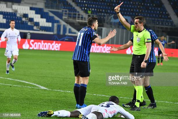 German referee Tobias Stieler gives a red card to Atalanta's Swiss midfielder Remo Freuler during the UEFA Champions League round of 16 first leg...