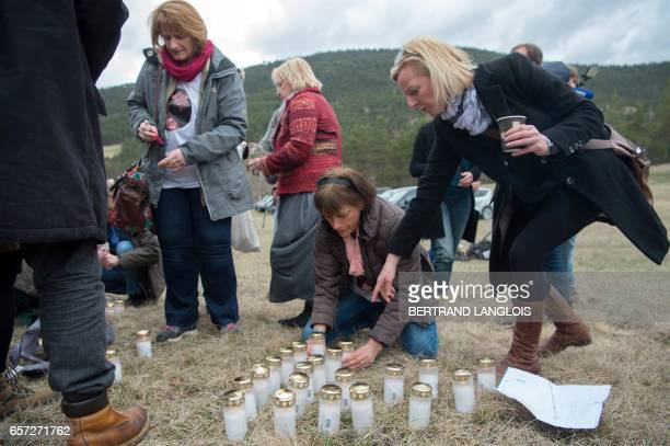 German relatives and friends of victims set candles during the commemoration ceremonies at the Vernet memorial southeastern France on March 24 2017...