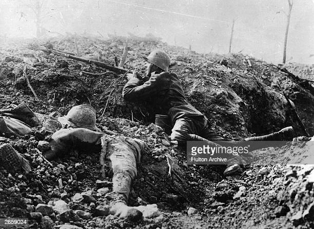 A German rifleman beside the corpse of a French soldier in a trench at Fort Vaux France