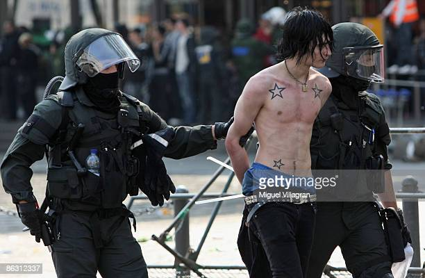German riot police detain a protestor in front of the railway station during a May day demonstration against a neoNazi demonstration on May 1 2009 in...