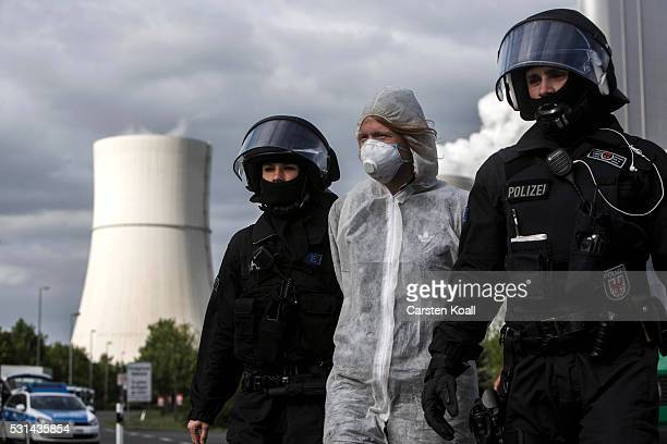 German riot police escort an anticoal activist that entered the grounds of the coal mine company Vattenfall factory Schwarze Pumpe on May 14 2016...