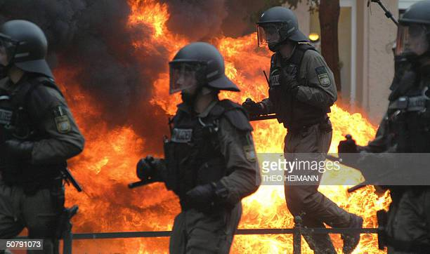 German riot police officers walk past a fire during clashes between rightist and leftist radicals in Berlin's Friedrichshain district 01 May 2004 AFP...